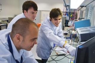 Drei junge Männer arbeiten an elektronischen Messgeräten