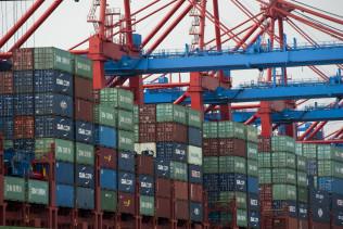 Mehrere Stapel von Containern in einem Hafen, darüber Ladekräne.