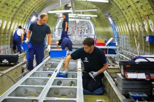Sechs Arbeiter beim Innenausbau eines Flugzeuges