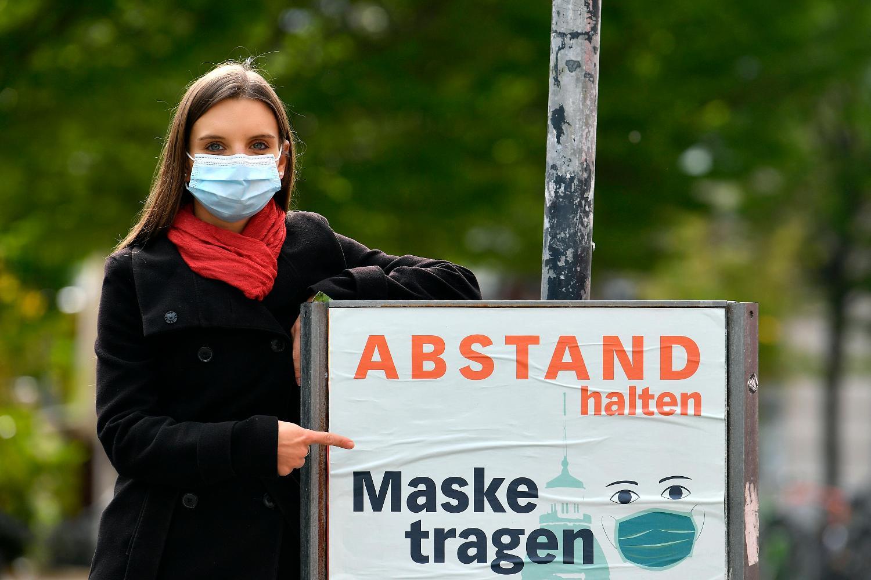 Eine junge Frau mit Mundschutz hält ein Plakat fest. Auf dem Plakat steht: Abstand halten. Maske tragen.