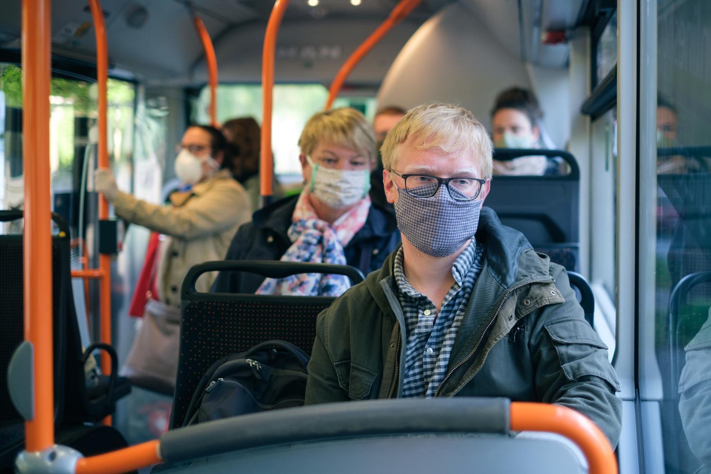 Menschen im Bus tragen einen Mund-Nasen-Schutz.