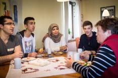 Ehrenamtliche und Flüchtlinge treffen sich beim gemeinsamen Frühstück
