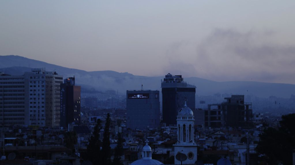 Smoke rises after airstrikes targeting different parts of the Syrian capital Damascus, Syria, early Saturday, April 14, 2018. (AP Photo/Hassan Ammar) |