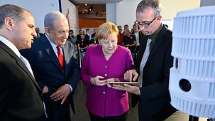 Chancellor Angela Merkel and Israel's Prime Minister Benjamin Netanyahu at an information stand