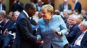 "Chancellor Angela Merkel greets Patrice Talon, President of the Republic of Benin, at the G20 ""Compact with Africa"" Investment Summit."