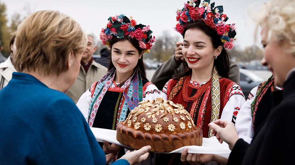 Chancellor Angela Merkel is given a traditional welcome in Kyiv with a gift of bread.