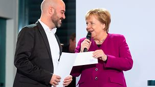 Chancellor Angela Merkel presents the award to Gal Rachman at the award ceremony for the National Integration Prize.
