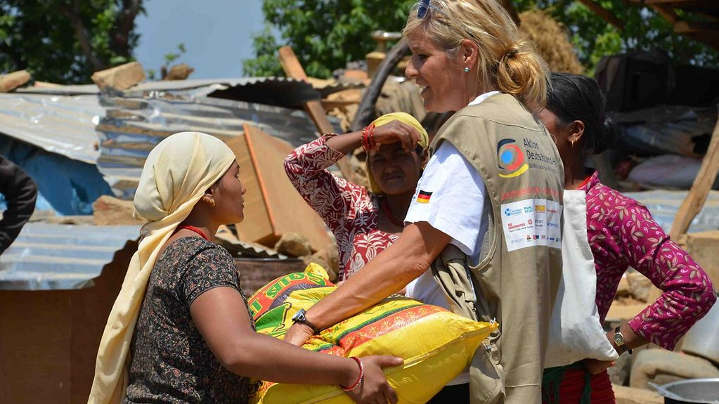 "A helper working for Germany's relief coalition ""Aktion Deutschland hilft"" gives an aid package to a Nepalese woman."