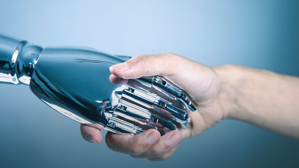 A robot hand shakes a human hand