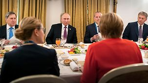 Angela Merkel speaks with Vladimir Putin.