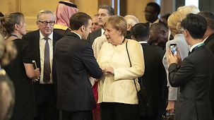 Angela Merkel speaks with Emmanuel Marcon.