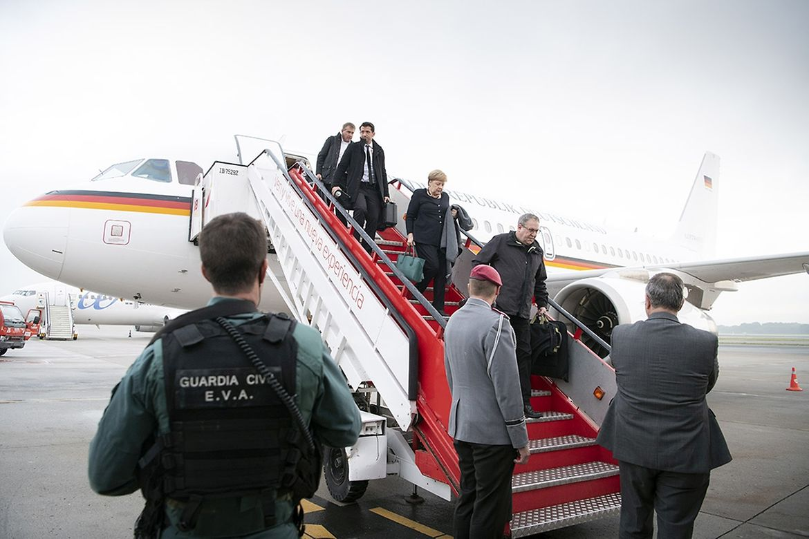 Chancellor Angela Merkel alights from the aeroplane.