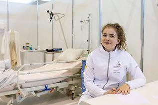 Elisabeth Hölscher sitzt in weißer Kleidung an einem Tisch, im Hintergrund ein Krankenhausbett