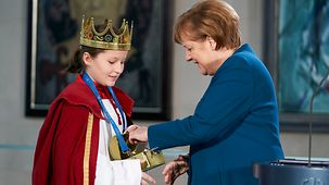 "Chancellor Angela Merkel puts her contribution into the collecting box at the reception for the ""Star Singers"" at the Federal Chancellery."