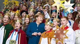 "Chancellor Angela Merkel sings with the ""Star Singers"" at the Federal Chancellery."