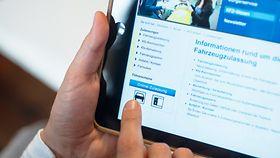 """Eine linke Hand hält ein iPad, auf dem die Webseite einer Kfz-Zulassungsstelle geöffnet ist. Die rechte Hand tippt auf eine Stelle auf dem Bildschirm, auf der """"Online-Zulassung"""" zu sehen ist."""