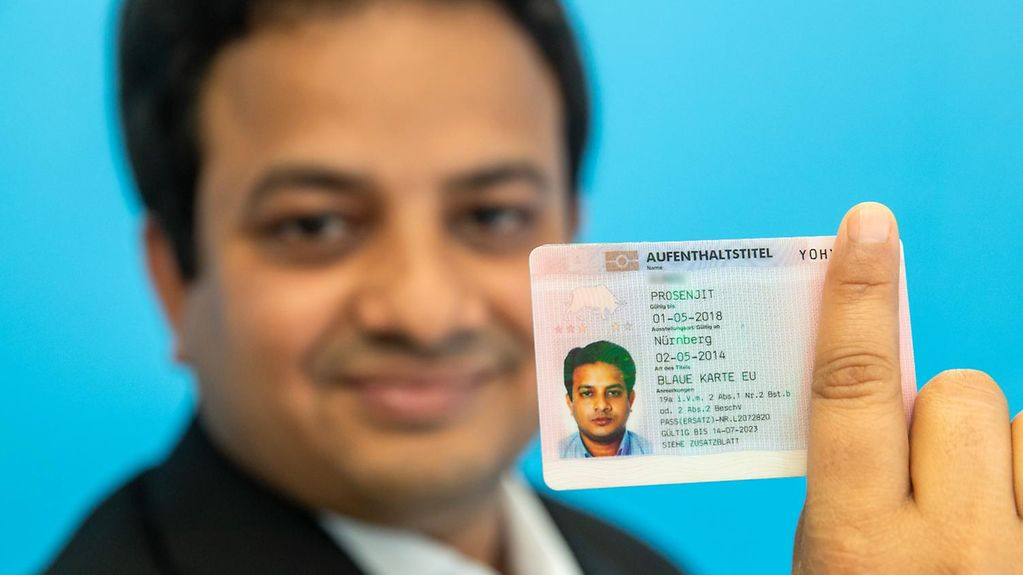 An Indian IT expert holds up his EU Blue Card.