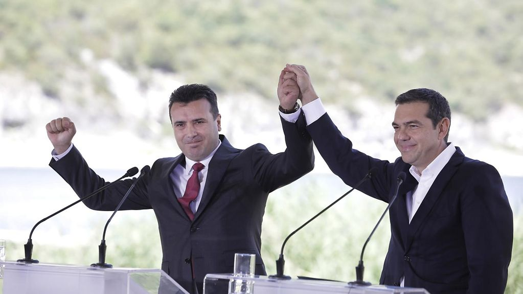 Greek Prime Minister Alexis Tsipras and Zoran Zaev, the Prime Minister of the former Yugoslav Republic of Macedonia, raise their joined hands in victory, as they stand at lecterns.