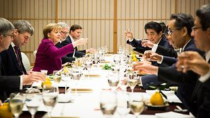 Chancellor Angela Merkel and Japan's Prime Minister Shinzo Abe raise their glasses for a toast.