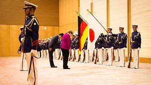 Chancellor Angela Merkel bows during the welcome with military honours.
