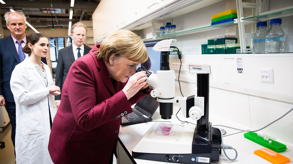 The Chancellor looks through a microscope in a BIMSB lab.