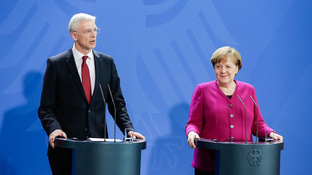Against a blue backdrop, Chancellor Angela Merkel and Latvian Prime Minister Krišjānis Kariņš each stand at a lectern during the press conference.