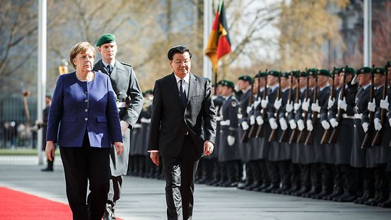 Chancellor Angela Merkel and the Lao Prime Minister walk along the red carpet as the Prime Minister is welcomed with military honours.