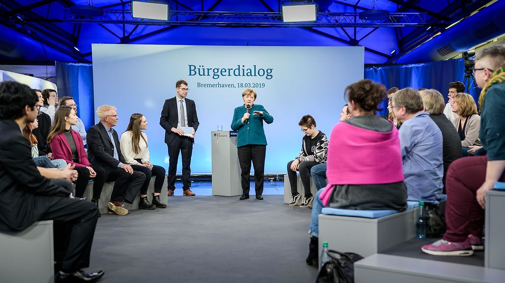 "Chancellor Angela Merkel stands in front of the audience, behind her a large screen that reads ""Citizens' Dialogue 18 March 2019""."