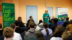 "The Federal Agriculture Minister Julia Klöckner stands at the front of a classroom beside a large green poster bearing the message ""Lust auf Natur"" (enjoy nature) and talks to students."
