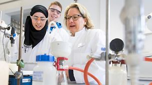 Federal Environment Minister Svenja Schulze performs an experiment in a laboratory of the Hans-Böckler-Berufskolleg with a student wearing a headscarf and a blond student.