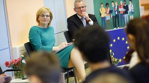 Julia Klöckner and a grey-haired gentleman sit in a classroom next to an EU flag during a discussion with students.