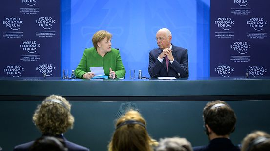 Chancellor Angela Merkel and Klaus Schwab, Executive Chairman of the World Economic Forum, sit in front of a blue background. In front of them the heads of the members of the audience.