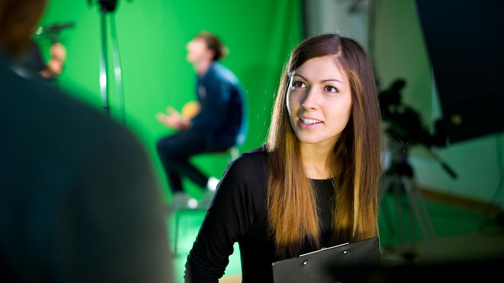 Trainee in a television studio, behind her a blurry man in a spotlight speaking to a camera