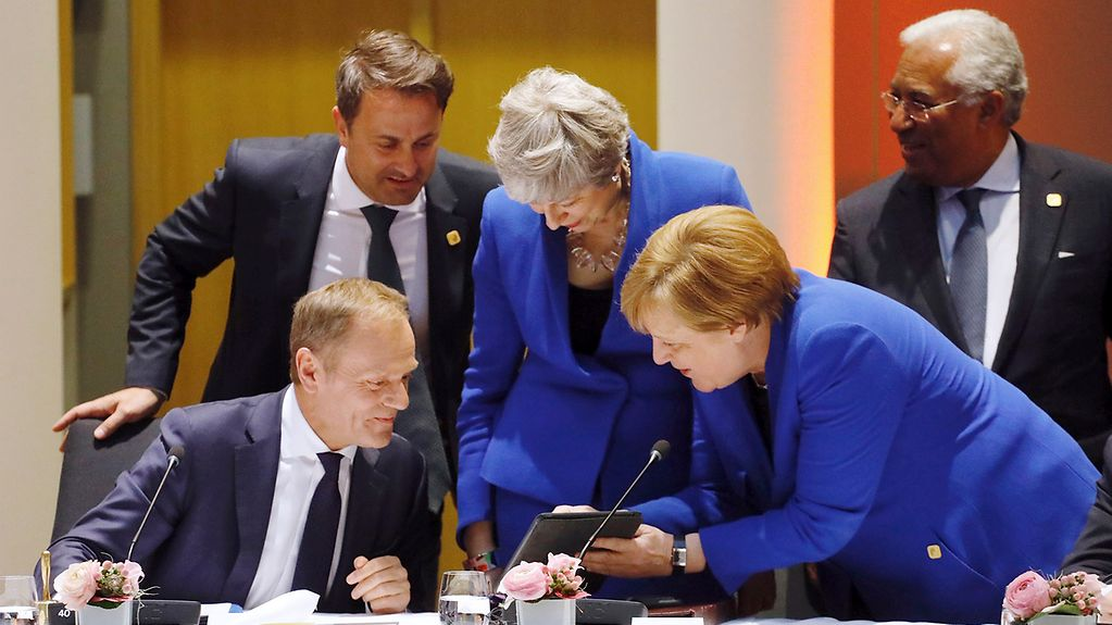German Chancellor Angela Merkel in conversation with Donald Tusk, President of the European Council, and British Prime Minister Theresa May.