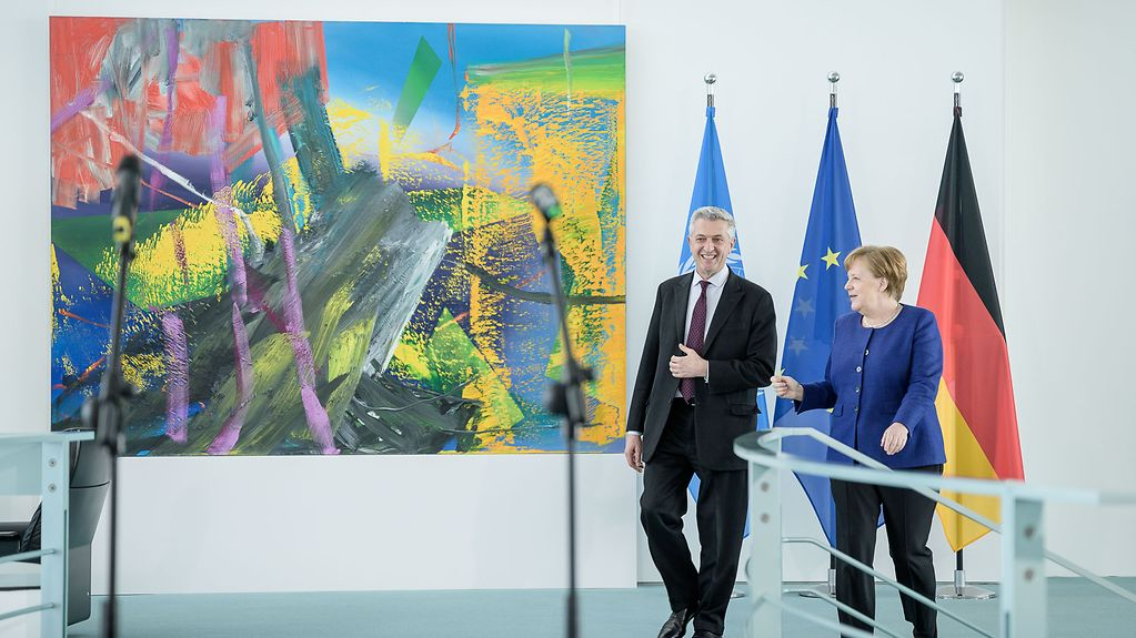 Chancellor Angela Merkel and UN High Commissioner for Refugees Filippo Grandi walk along a corridor in the Federal Chancellery. Behind them are the German, EU and UN flags and a painting on the wall.