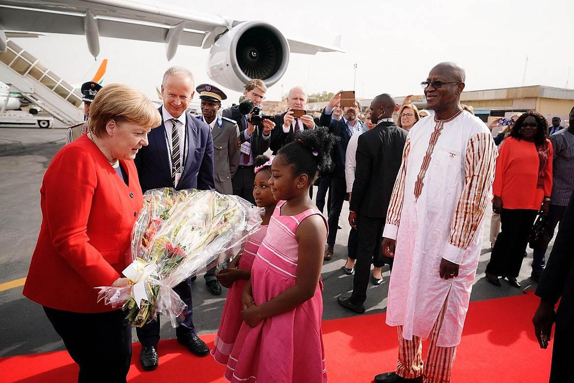 On her arrival in Burkina Faso, Chancellor Angela Merkel is welcomed with bouquets of flowers.
