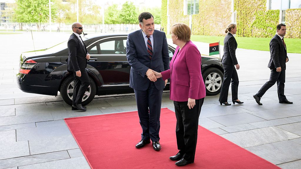 Chancellor Angela Merkel and Fayez al-Sarraj shake hands on the red  carpet. The Chancellor has turned away from the camera. In the background stands a limousine.