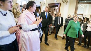 Chancellor Angela Merkel walks with Romania's President Klaus Iohannis in Sibiu.