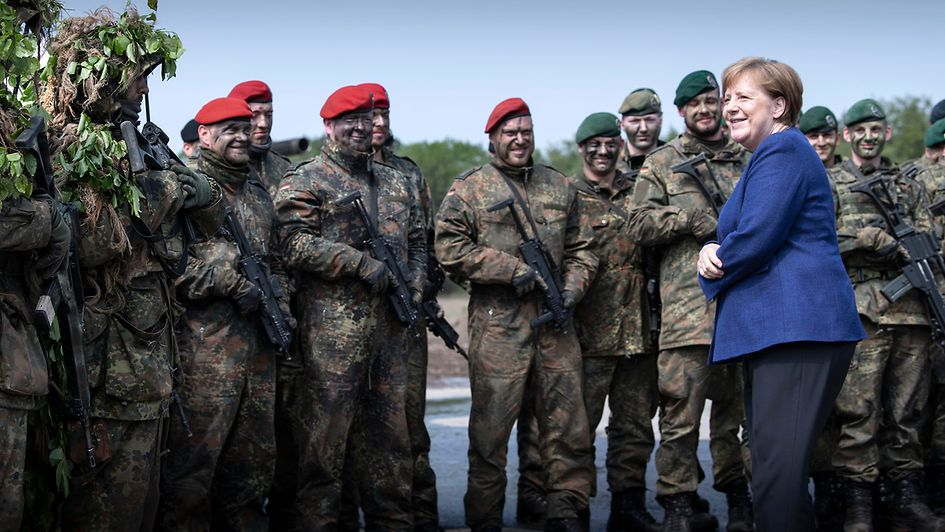 Chancellor Angela Merkel talks to soldiers during her visit to the Very High Readiness Joint Task Force Land.