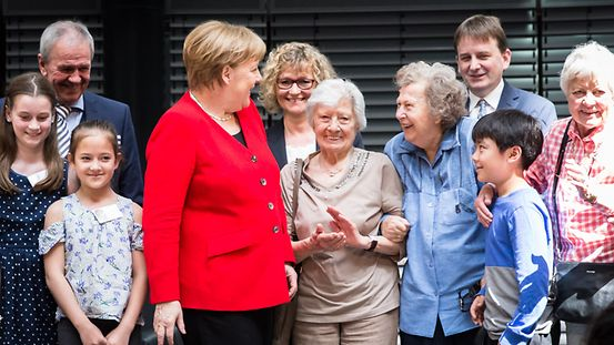 "Chancellor Angela Merkel with pensioners and children at the celebrations to mark the 10th anniversary of the ""Generationsbrücke Deutschland"""