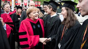 Chancellor Angela Merkel shakes hands with Harvard graduands before the Commencement ceremony.