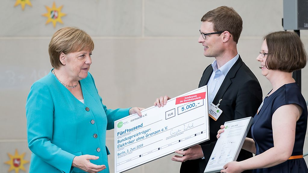 The Chancellor presents a cheque for EUR 5,000 to representatives of Elektriker ohne Grenzen (Electricians without Borders)