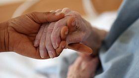 Eine Pflegerin hält im Caritas-Altenheim in Köln die Hand einer Bewohnerin.