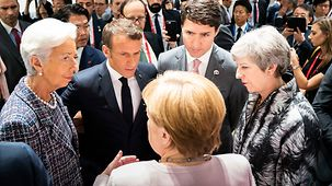 Chancellor Angela Merkel in conversation with Christine Lagarde, Managing Director of the International Monetary Fund, French President Emmanuel Macron, Canadian Prime Minister Justin Trudeau and British Prime Minister Theresa May