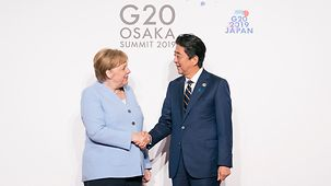 At the G20 summit in Osaka Chancellor Angela Merkel is greeted by Japan's Prime Minister Shinzo Abe.