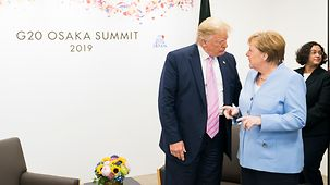 Chancellor Angela Merkel in conversation with President Donald Trump at the G20 summit in Osaka