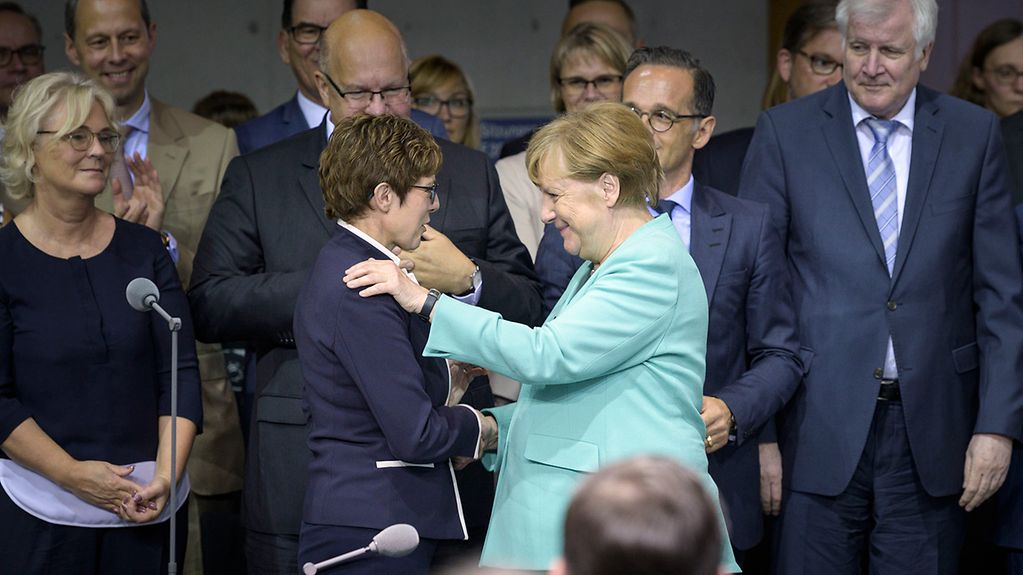 Angela Merkel congratulates Annegret Kramp-Karrenbauer with a handshake.