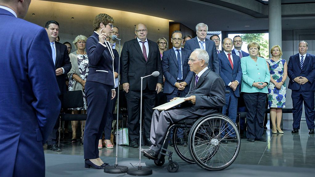 Kramp-Karrenbauer raises her hand to take the oath and Wolfgang Schäuble stands opposite her.