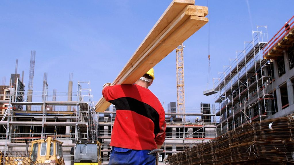 A construction worker carries wooden planks across a building site.