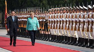 China's Prime Minister Li Keqiang welcomes Chancellor Angela Merkel with military honours.
